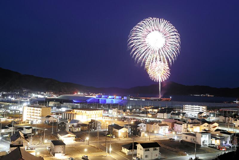 2021年3月11日午後6時18分。岩手県大槌町にて、夜空に約700発の「鎮魂と希望の花火」が打ち上がり、高台にのぼった住民らから歓声があがった光景。眼下には整備の続く町並みが広がる